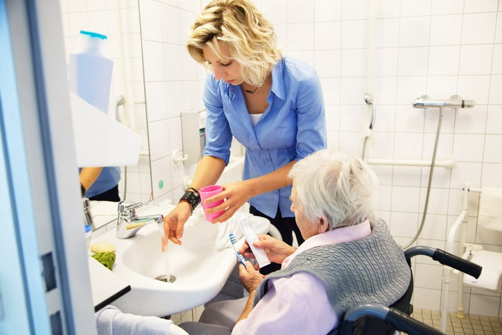 home health care nurse helping senior woman in wheelchair in bathroom, assisting with teeth cleaning