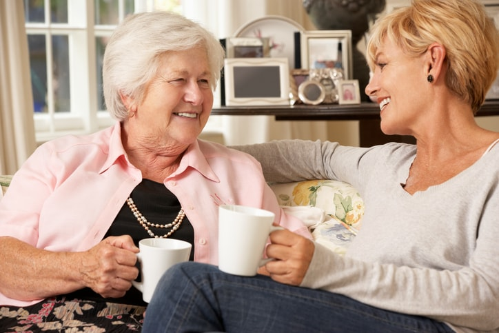 Adult daughter and senior mother sitting on sofa at home having a chat about home care whilst drinking tea