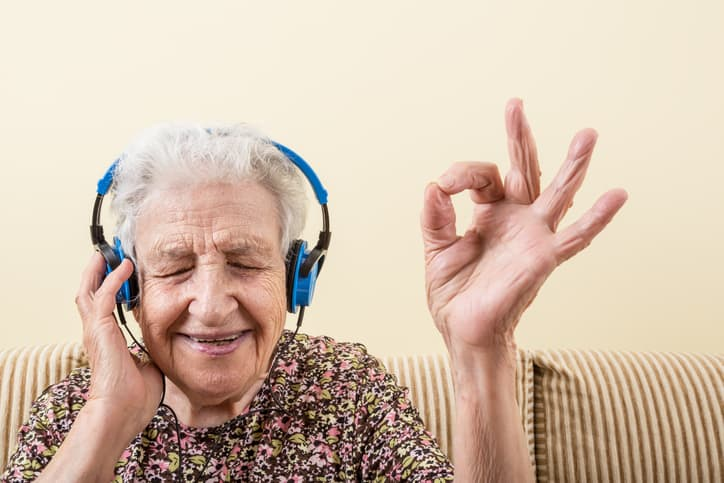 senior woman with Parkinson's making okay sign while wearing headphones to listening music