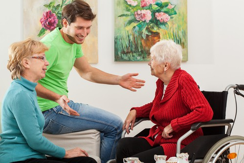 Young man and woman family talking with senior grandmother about home health care