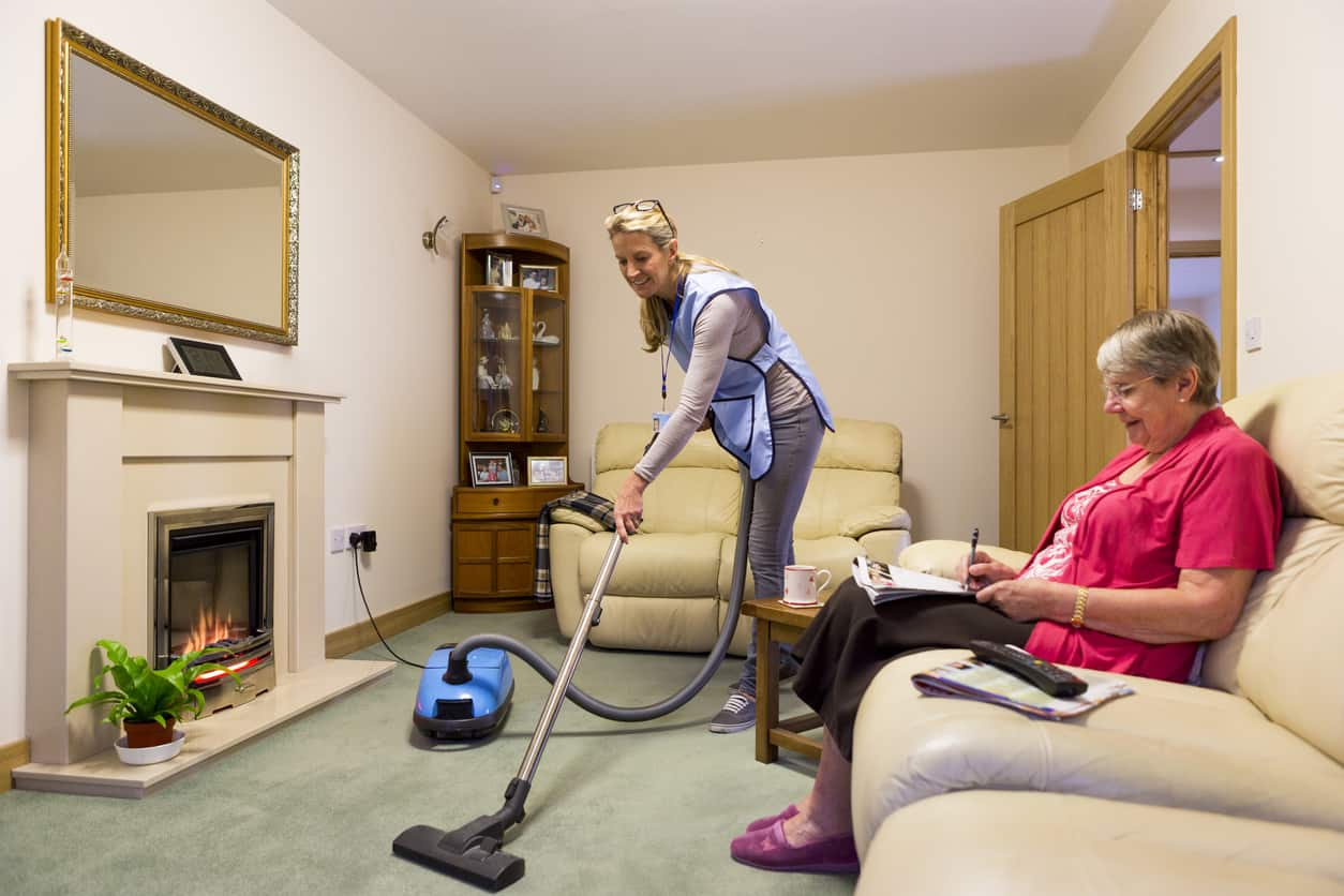 Home Health Care worker making a home visit. Female carer is hoovering the living room to help an elderly woman. The woman is sitting on a sofa relaxing
